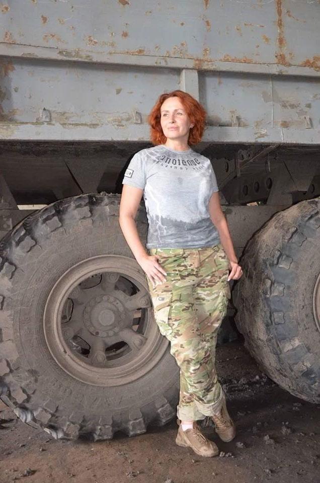 Юлія Кузьменко позує в камуфляжних штанах на фоні колеса